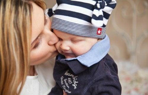 Mama całuje dziecko w policzek