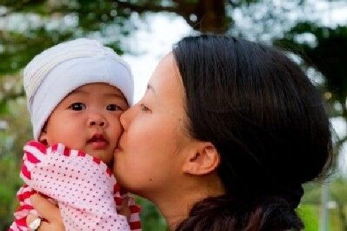 Matka czule całuje dziecko w policzek - tęczowe dziecko
