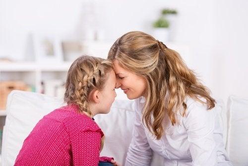 Mama czule przytula się czołem do córki