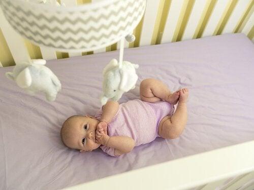 Noworodek patrzy na karuzelę nad łóżeczkiem