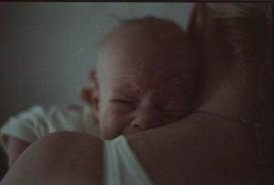 Płaczące dziecko w ramionach matki
