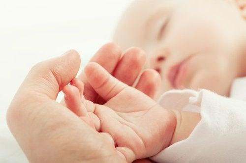 Śpiące niemowlę położyło rączkę na dłoni mamy