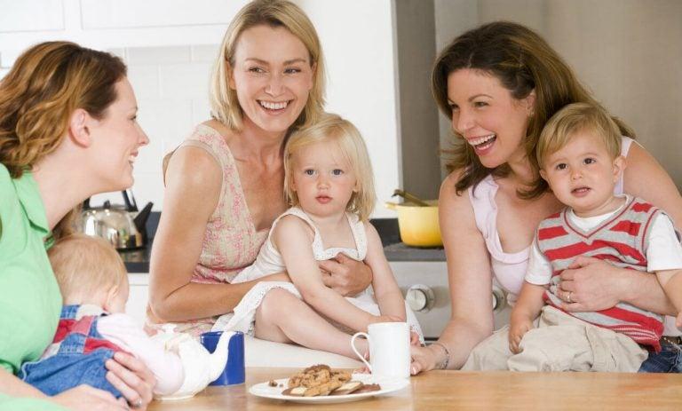 Radosne kobiety z dziećmi przy stole