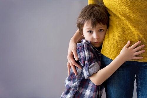 Chłopiec przytulający się do nogi mamy