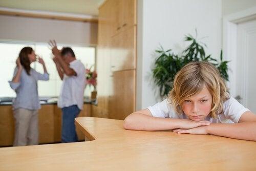 Chłopiec siedzący z głową leżącą na stole opartą na rękach, w tle kłótnia rodziców