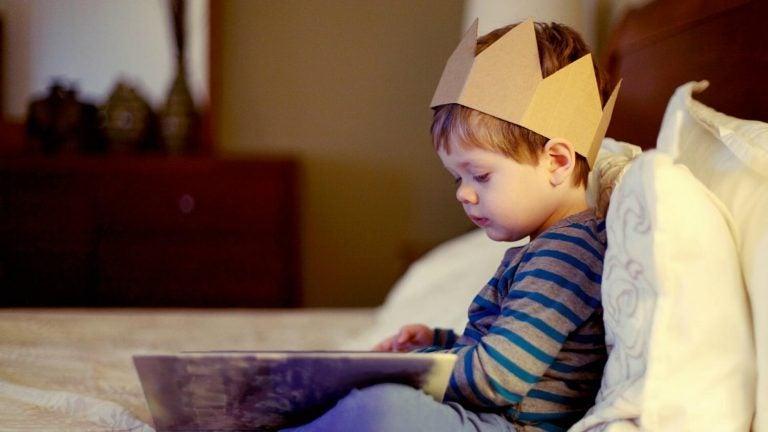 Chłopiec z koroną na głowie czytający książkę