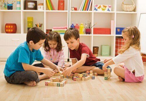 Czwórka dzieci siedząca na podłodze i układająca klocki