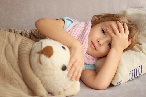 Dziecko leżące z misiem trzymające się za głowę