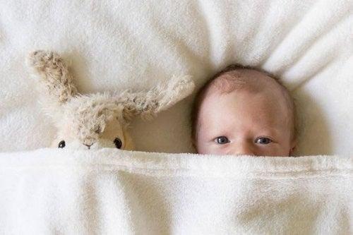 Dziecko patrzy z pod kołdry