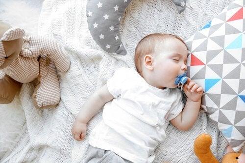 Dziecko śpiące na plecach ze smoczkiem w ustach, uczące się jak przespać całą noc