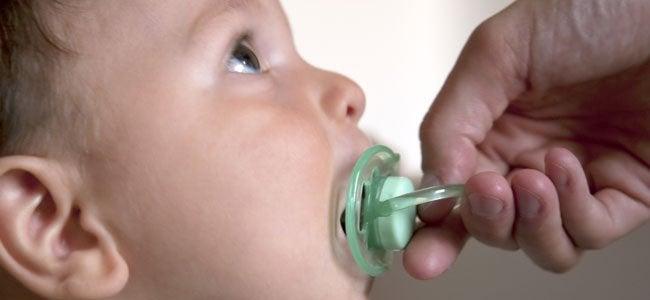 Dziecko ssące smoczek trzymany w ręku przez rodzica - nadmierne używanie smoczka