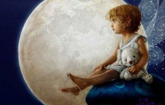 Dziewczynka z pluszowym misiem siedząca na tle księżyca