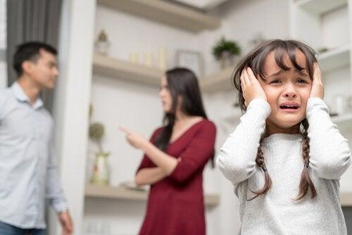 Dziewczynka zakrywająca uszy rękoma, w tle kłócący się rodzice - kłótnie w obecności dzieci