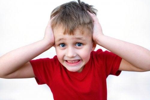 Krzyczące dziecko trzymające się za głowę