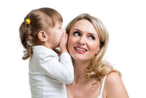 Mała dziewczynka szepcząca mamie do ucha