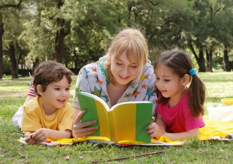 Mama leżąca na trawie z dwójką dzieci, czytająca im książkę