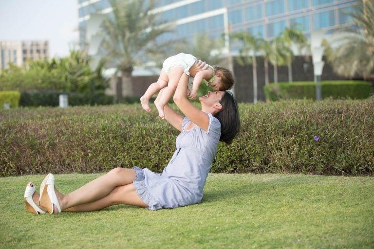 Mama siedząca na trawie podnosząca niemowlę - jak świętować pierwsze urodziny Twojego dziecka