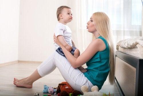 Mama trzymająca dziecko na kolanach podczas nauki mówienia, dbająca o rozwój mowy dziecka