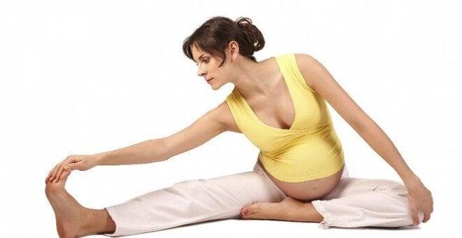 Mama w ciąży rozciągająca mięśnie nóg