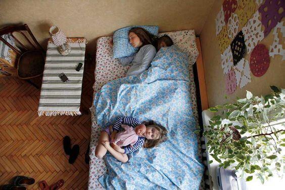 Przytuleni mama i tata śpiący z dzieckiem - wychowanie dziecka jest męczące dla kobiet
