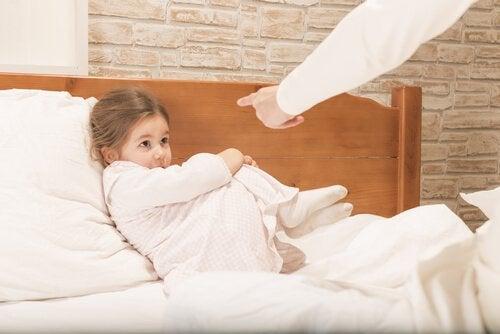 Ręka grożąca palcem dziewczynce leżącej na łóżku