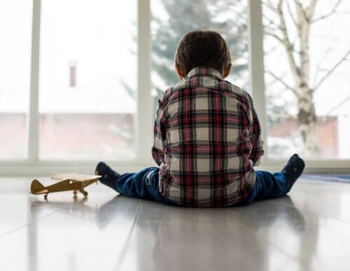 Smutne dziecko siedzące na podłodze odwrócone plecami