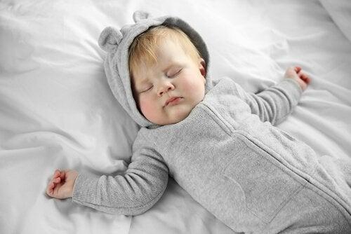 Śpiące niemowlę w piżamce z kapturem z uszkami