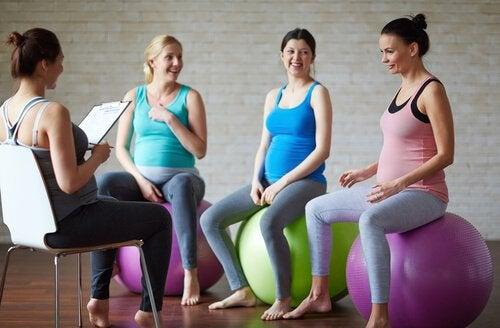 Trzy kobiety w ciąży siedzące na dmuchanych piłkach i trenerka siedząca na krześle