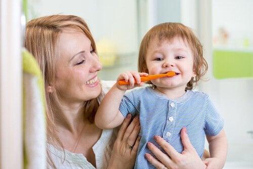 Uśmiechnięta mama przytulająca dziecko samodzielnie myjące zęby