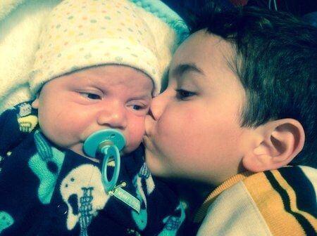 Chłopiec całujący niemowlę w policzek - zazdrość o młodsze rodzeństwo