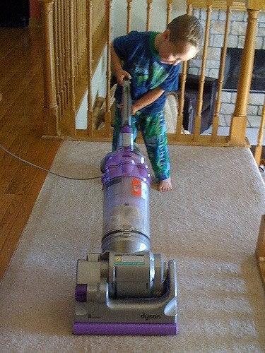 Chłopiec odkurzający dywan, wykonujący obowiązki domowe