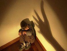 Chłopiec skulony w rogu, chowający się przed cieniem ręki na ścianie
