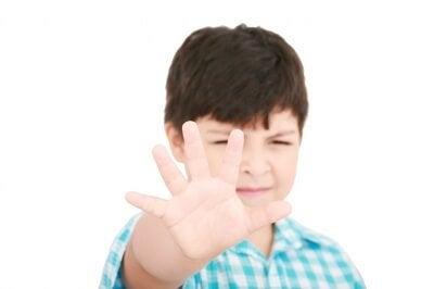 """Chłopiec wyciągający przed siebie rękę w geście """"stop"""""""