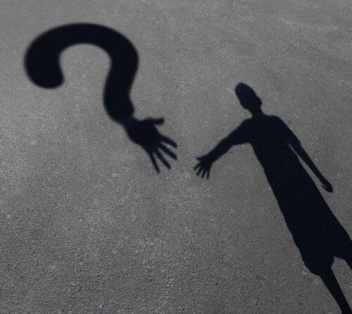 Cień chłopczyka, który chce sięgnąć ręką znak zapytania