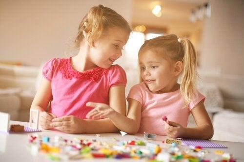 Dwie dziewczynki układające klocki LEGO na stole