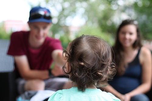 Dziecko obrócone tyłem patrzące na rodziców w tle