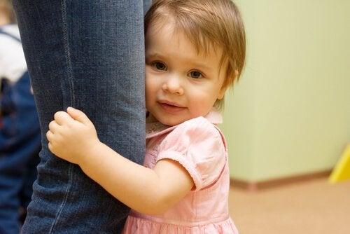 Mała dziewczyna trzyma nogę swojej mamy