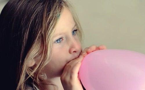 Dziewczynka dmucha balon