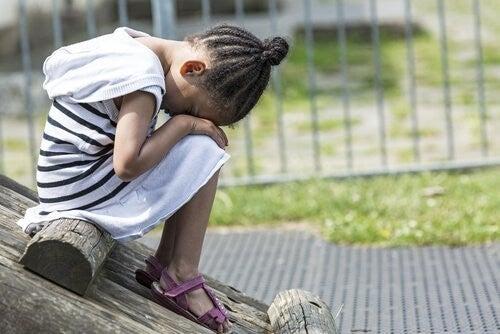 Smutna dziewczynka, która siedzi ze schowaną twarzą