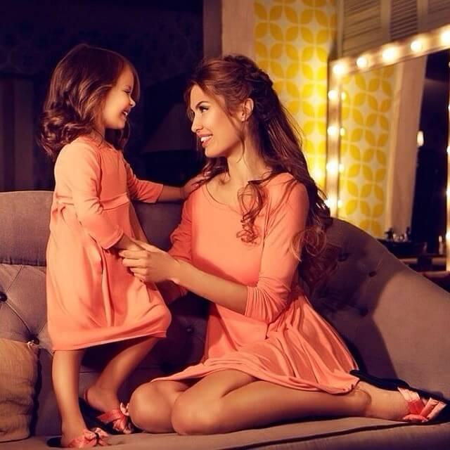 Dziewczynka stojąca na kanapie trzymająca za rękę mamę siedzącą na kanapie