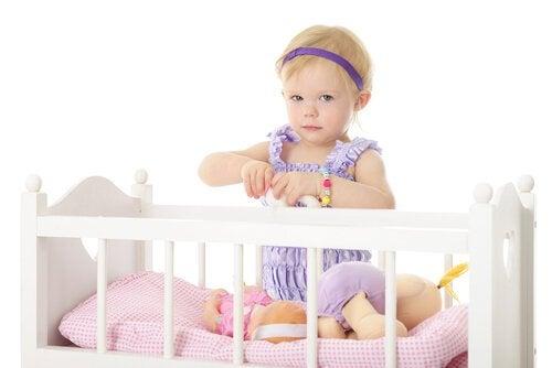 Dziewczynka bawiąca się w łóżeczku