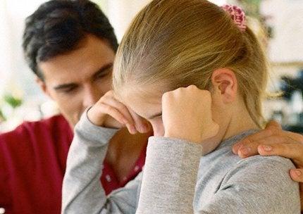 Dziewczynka z głową podpartą na rękach i gładzący ją po plecach tata