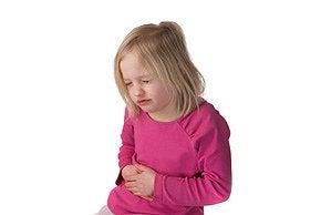 Dziewczynka z grymasem na twarzy, trzymająca się za brzuch - objawy choroby