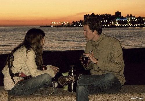 Kobieta i mężczyzna siedzący na murku o zachodzie słońca i pijący piwo