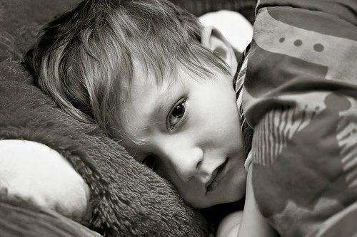 Leżący chłopiec przykryty kołdrą
