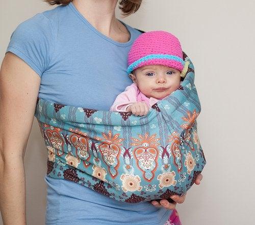 Mama nosząca niemowlę w chuście