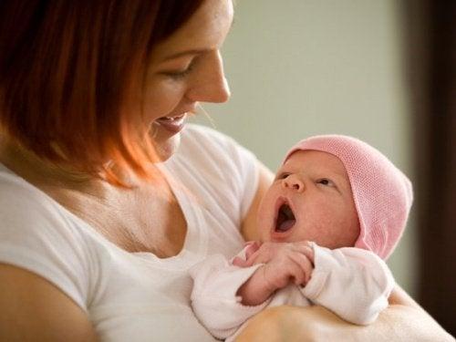 Mama uśmiechająca się do przytulanego niemowlaka