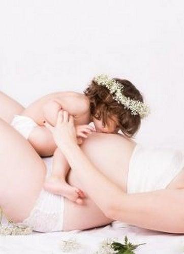 Mama w ciąży trzyma dziecko, które całuje jej brzuch