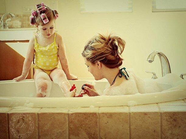 Mama w wannie malująca paznokcie u stóp córki siedzącej na rancie wanny