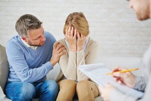 Mąż pociesza żonę, która zakrywa twarz na wizycie u lekarza